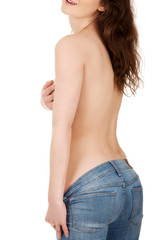 Shirtless woman in jeans covering breast.