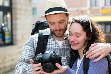 Young couple of tourist watching photographs on camera