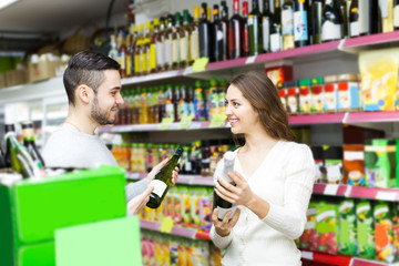 shoppers choosing bottle of wine at liquor store