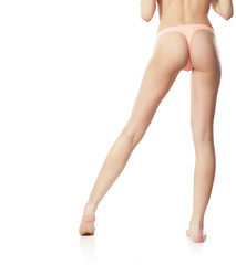 naked female legs and cute butt in pink panties on a white