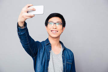 Happy young asian man making selfie photo