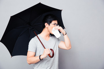 Sick asian man holding umbrella and blowing nose