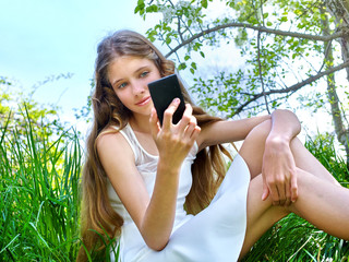 Girl do selfie snapshot blossoming tree.
