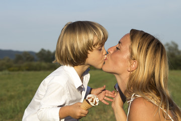 Young boy kissing his cute mother on sunny summer day