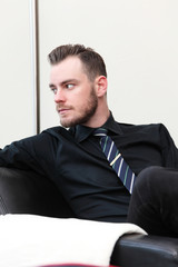 Relaxed businessman sitting down in an arm chair indoors