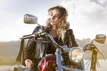 Biker girl in  leather jacket on a motorcycle looking at the