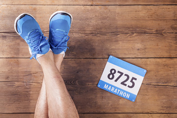 Legs of a runner on a wooden floor background