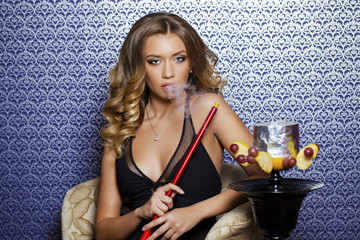 Beautiful young curly blonde woman resting in the hookah room