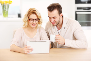 Happy couple using tablet at home