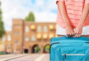 Cruise. Woman in blue dress holds orange suitcase in hands on