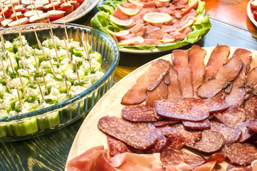 Sliced sausages and cocktail bites in dishes