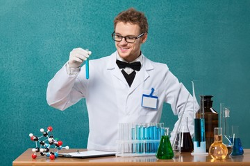 Adult. Mad professor laughs handing test tube in his laboratory