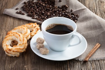 Coffee cup with coconut cookies, cinnamon and cane sugar