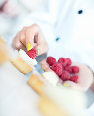 Chef hands decorating cupcakes