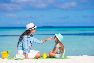 Mother applying sun protection cream to her daughter at tropical