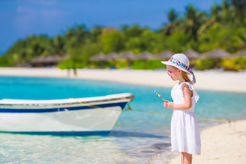 Adorable little girl with lollipop on tropical beach