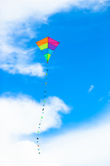 Colorful kite flying in the wind background blue sky