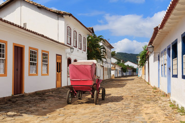 Coach on street, old colonial houses in Paraty, Brazil
