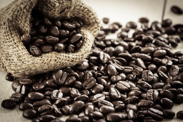 Wall Murals Coffee beans Roasted coffee beans in bag on wooden background in vintage colo