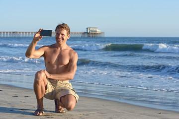 Man takes selfie at beach