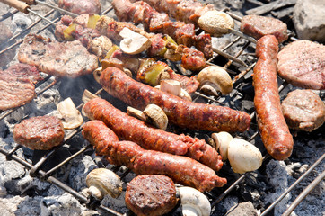 Beef steaks and sausages cooking in open flame on barbecue grill
