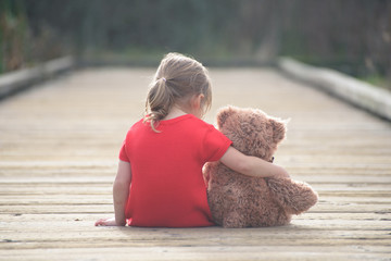 Girl in red dress sitting with teddybear on boardwalk