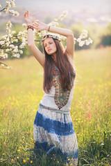 Beautiful hippie woman dancing in a summer field