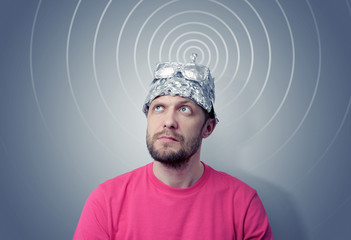 Bearded funny man in a cap of aluminum foil sends signals
