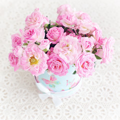 Beautiful fresh pink roses on a light background .