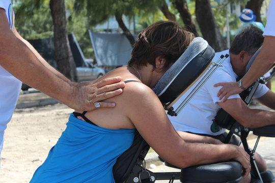 Mulher sendo massageada na cadeira de Quick Massagem
