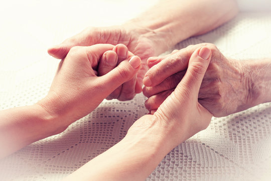 Care is at home of elderly. Hands senior man and caregiver.