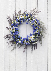 Wreath of flowers on the wooden background