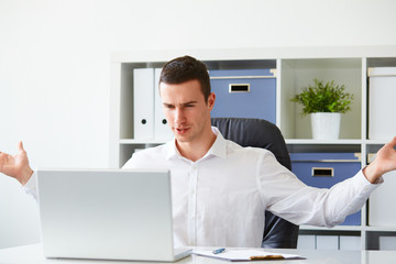 Businessman is angry while working on laptop