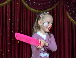 Laughing little girl in comic makeup