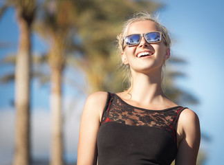 Smiling woman with trendy sunglasses on the holidays
