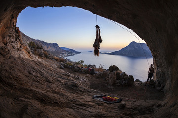 Female rock climber hanging on rope upside down