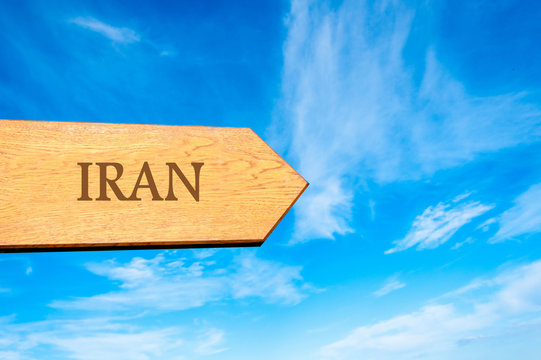 Wooden arrow sign pointing destination IRAN