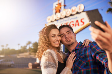 romantic couple taking selfie by las vegas sign
