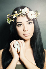 Beautiful brunette woman with cotton flowers in her hair and han