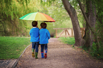 Two adorable little boys, walking in a park on a rainy day, play