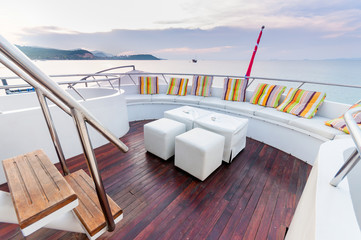 White stools and long seat on the yacht deck