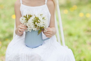 for spring bouquet of flowers with blue jug held by a child