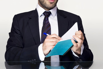 Businessman writing in notebook