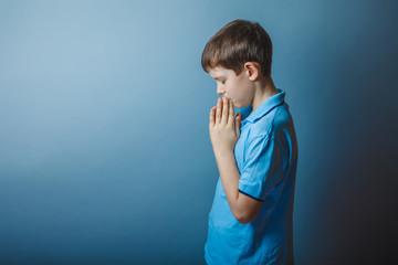 boy teenager European appearance in a blue shirt brown praying c