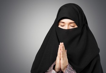 Hijab. Mysterious middle eastern woman praying on black