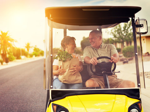 active elderly senior couple getting groceries on golf cart