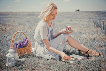 Young beautiful woman drinking tea and reading books outdoors