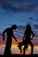 silhouette of a cowgirl hold saddle hand on hip
