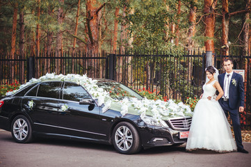 The bride near a black wedding car