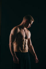 muscular young man showing his biceps isolated on black